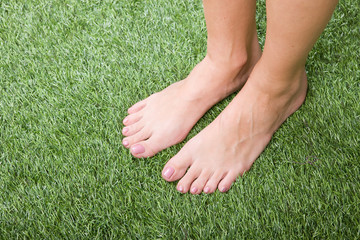 Beautiful slim female feet on green grass