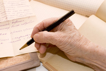 The old hand writes the letter a pencil