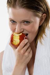 Blonde Frau isst roten Apfel der Sorte Elstar