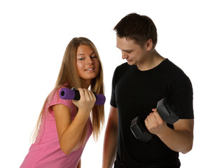 Young man and the girl with dumbbells