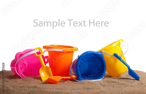 Assorted colored buckets on sand with copy space