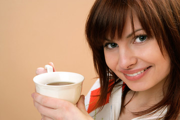 Portrait of young happy woman holding cup with tea