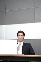 mann in anzug sitzt vor notebook und surft in büro