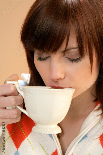 Woman drinking tea with closed eyes