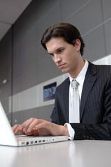 geschäftsmann in anzug tippt und surft mit laptop