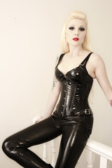 A sexy blonde model wearing black shiny latex