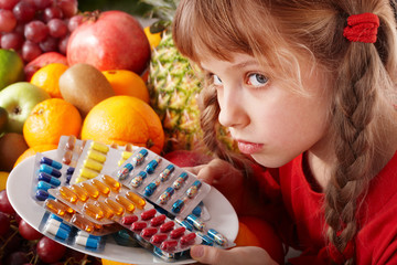 Child with fruit and vitamin pill. Health care.