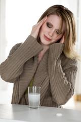 Frau hat Kopfschmerzen und nimmt Brausetablette