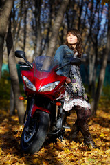 The mysterious girl about a red motorcycle among the autumn natu