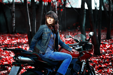 The mysterious girl on a red motorcycle among the fantastic red