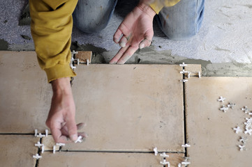 Closeup of a male hands working at a new floor tiles.