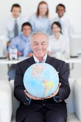 Senior businessman holding a terrestrial globe