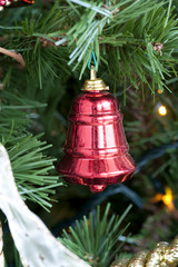 Detail of a decorative red bell on the Christmas tree
