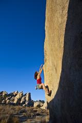 Young woman rock climbing.
