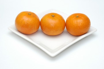 Three mandarins on white square plate