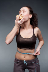 sporty woman eating cake with pleasure