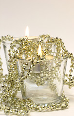 Two candles in glass with golden decoration beads