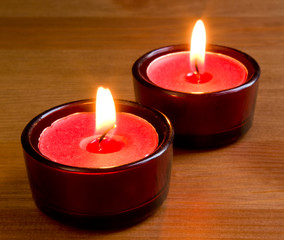 lit pink tea light candles on wooden table