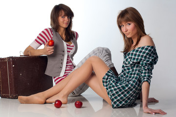 Two Young Sexy Girls lying with red apple and grunge suitcase