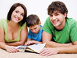 preschool boy reading book with his  parents