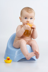 Infant on potty with bottle.