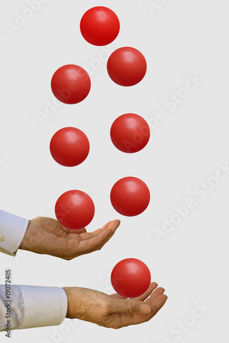 Businessman with many balls in the air - on grey