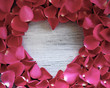 Old wooden heart with rose petals