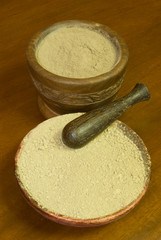 mortar and a wooden plate with Ayurvedic powders
