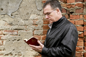 Man with Bible by Old Brick Wall