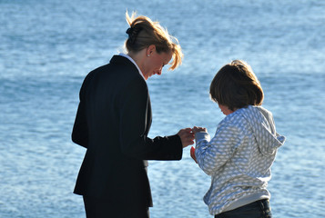 Mother and son collecting shells at the beach