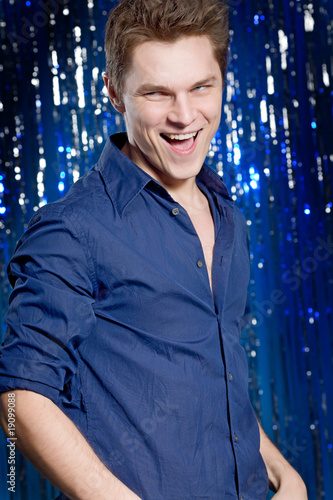 Young happy man over blue background