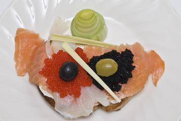 Tosta con caviar, ahumados y aceitunas.