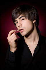 Young  man with toothpick in black shirt on red background