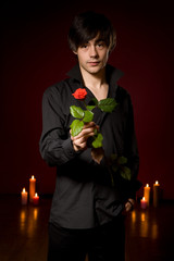 Young  man with rose in black shirt on red background with candl