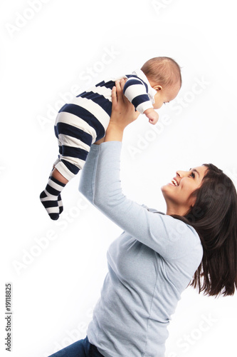 Happy mom lifting up baby son
