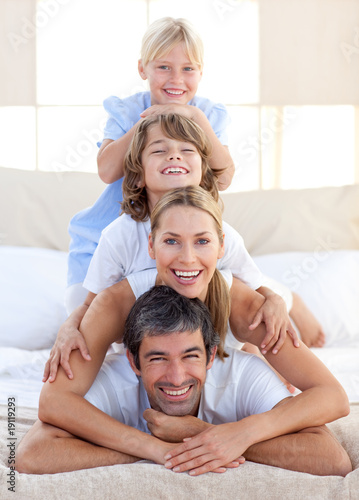 Happy family having fun on a bed