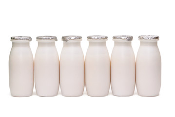 Row of six plastic bottles with milk isolated
