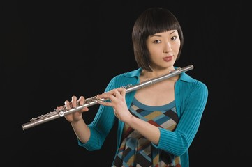 Portrait of young Korean woman holding flute