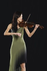 Young Asian woman stands playing the violin