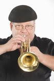 Mature man in flat cap playing the trumpet
