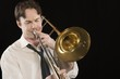 Mid-adult man with open-collar shirt plays the trombone