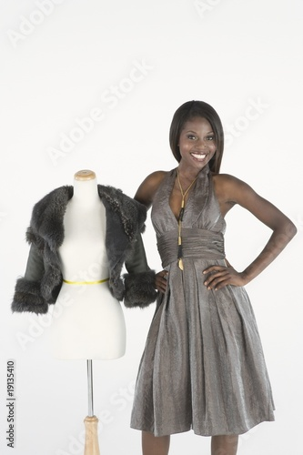 Fashion model stands beside tailor's dummy with fake fur bolero jacket
