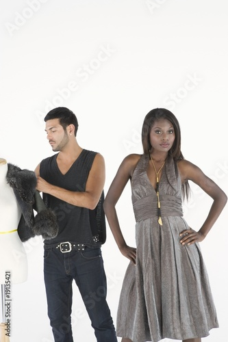 Fashion stylist adjusts jacket on mannequin while model stands with hands on hips