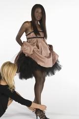 Fashion stylists adjusts models footwear