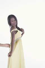 Model in yellow dress is helped with zip