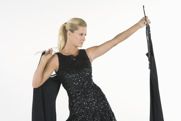 Woman holds up black dress, choosing what to wear