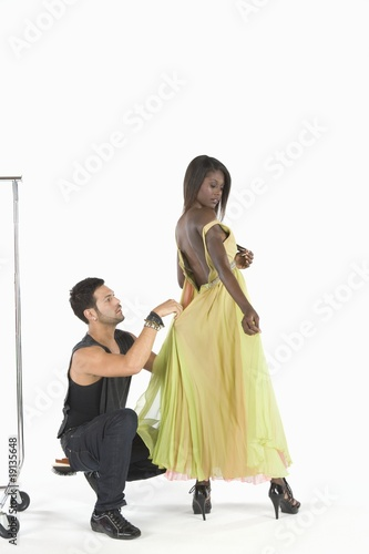 Stylist adjusts dress in fitting