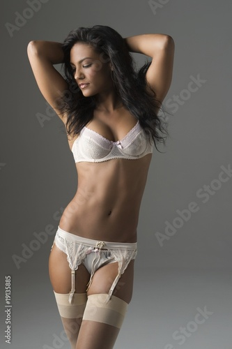 Woman stands in underwear and suspenders