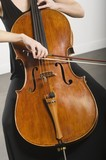 Mid section of woman bowing a cello