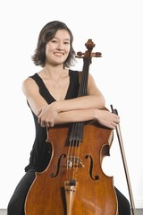 Female cellist sits with arms folded across cello